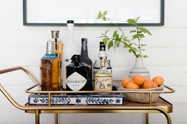 a bar cart with liquor, oranges, and a plant.