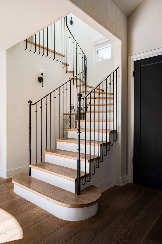 elongated balusters that attach to black stair railing with wood steps