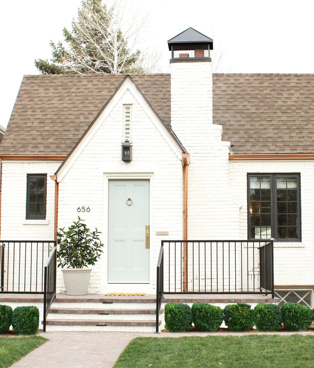 Traditional brick home painted white with blue front door