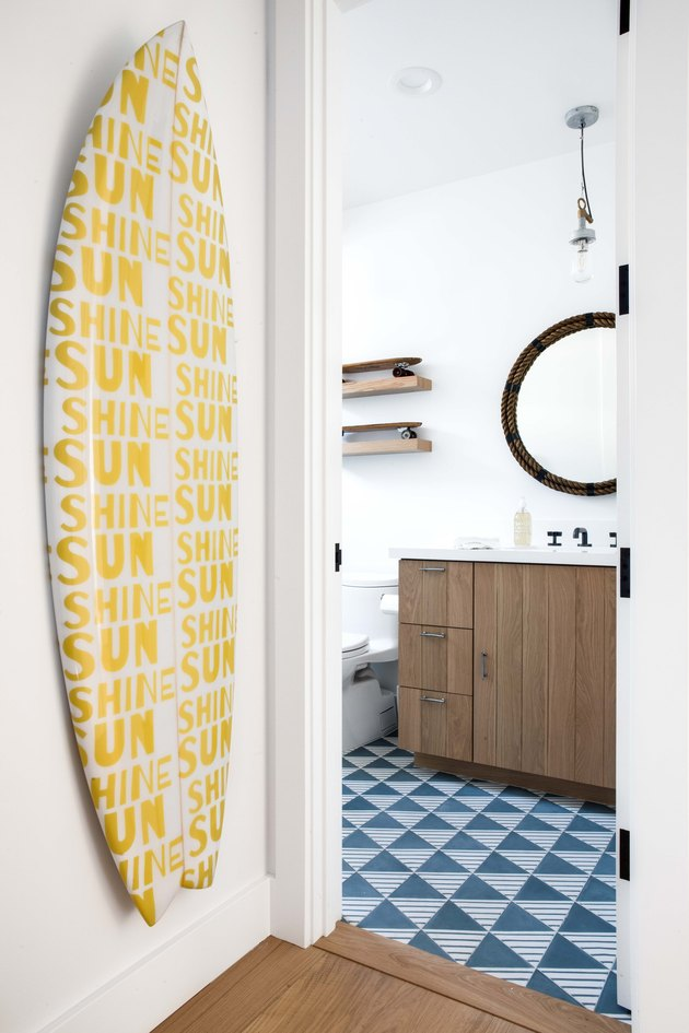 Yellow and white surfboard on wall next to bathroom with patterned floor tile
