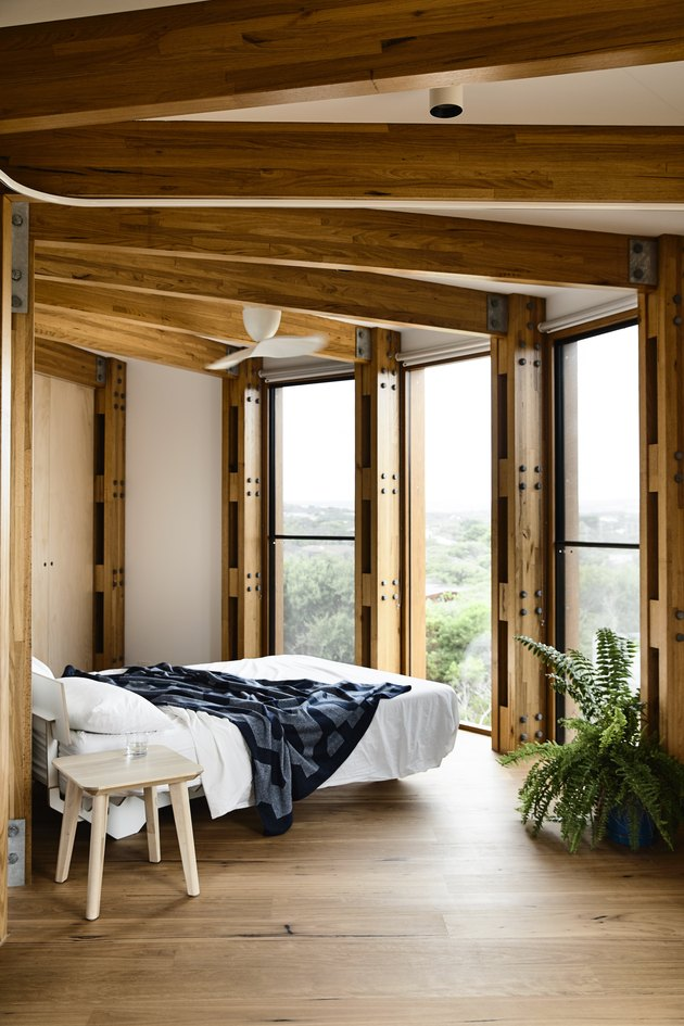wooden bedroom with floor to ceiling windows and bed
