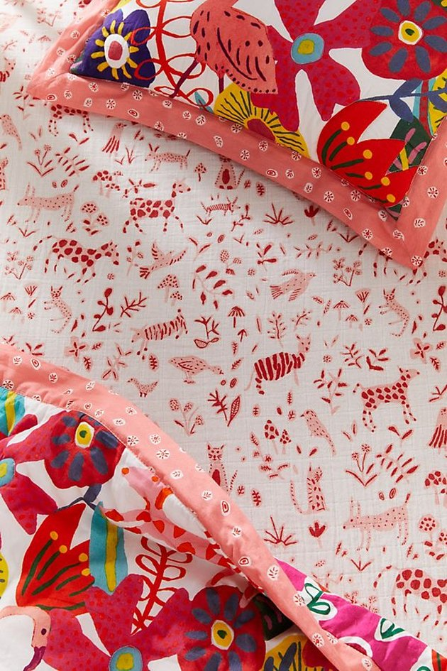 childrens' crib sheet in a bright pattern with animals