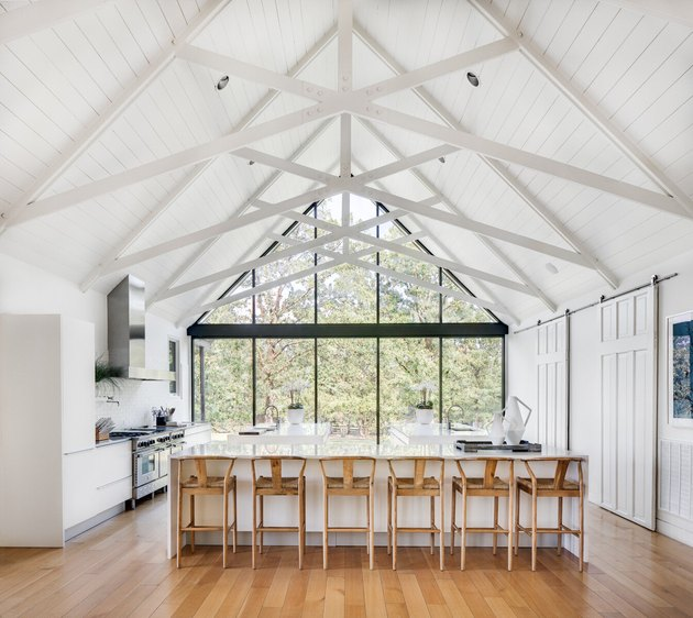 cathedral ceiling with floor to ceiling windows and beams in the kitchen