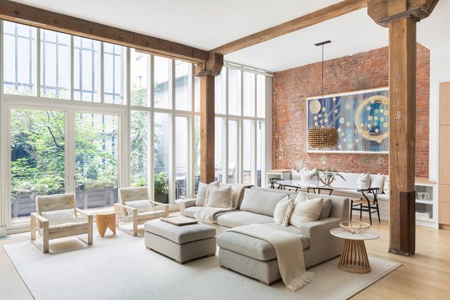 large loft with a wall of floor to ceiling windows and exposed brick wall