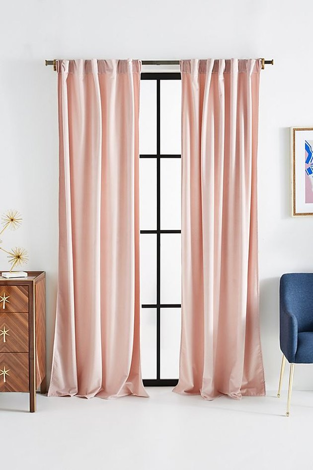 space with light pink velvet curtains and a tall window