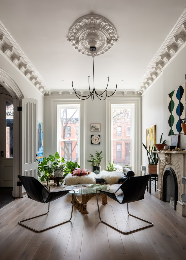 white living room with floor to ceiling windows and classic molding