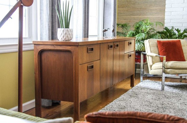 vintage vintage living room idea with sideboard in front of a window in a mid-century living room