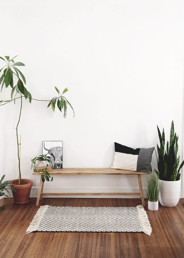 white room with wood floors and diy rustic decor wooden bench