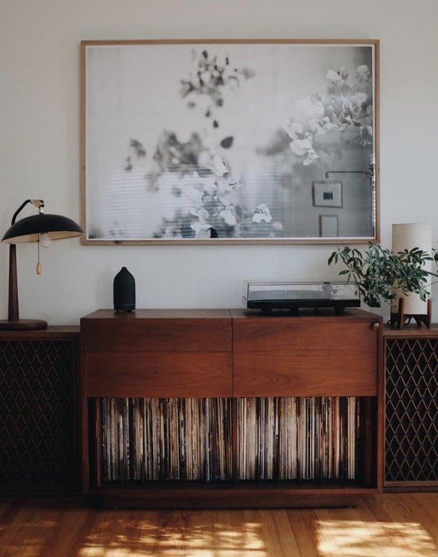 vintage living room idea with record cabinet under a framed black and white abstract art prin