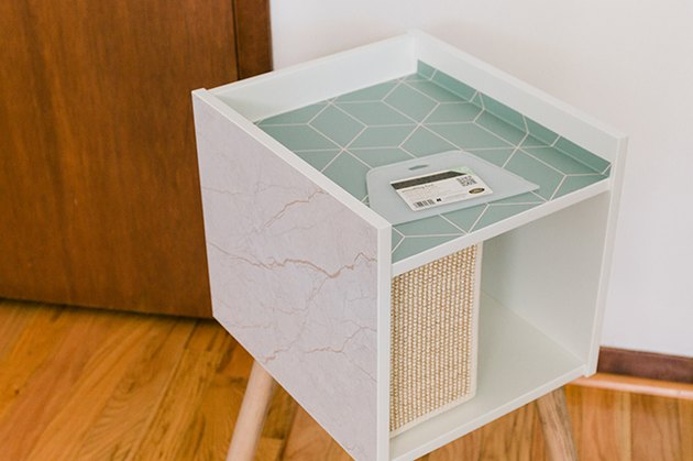 Stick the cut patterned shapes to the top and sides of the IKEA cat house.