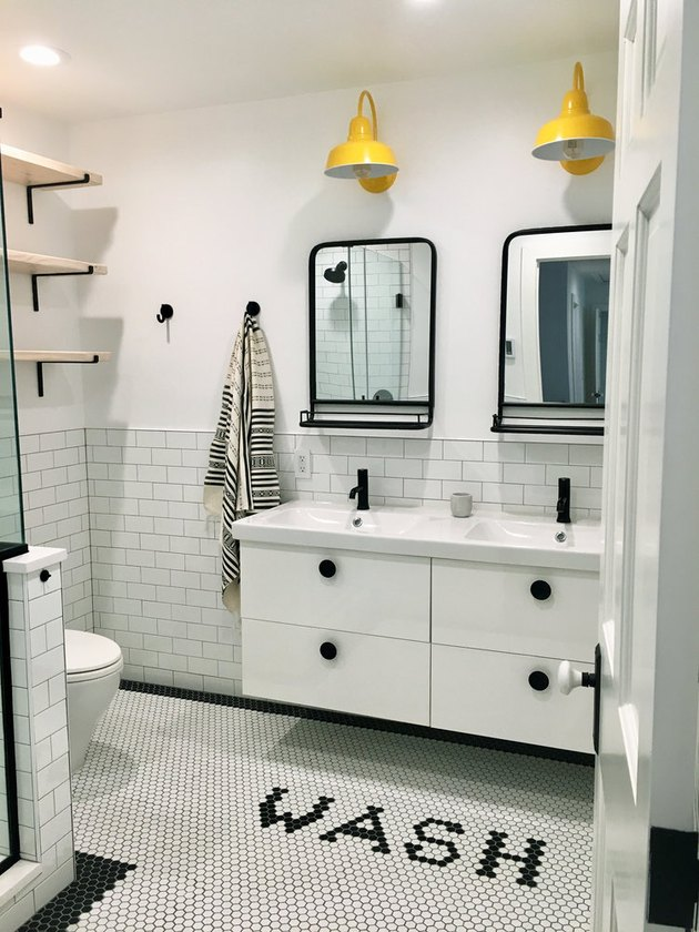 quirky bathroom floor tile idea in white bathroom with yellow wall sconces