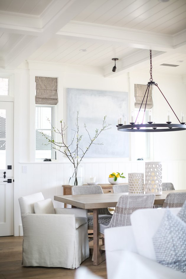rustic beach decor in dining room with modern black chandelier and wood dining table