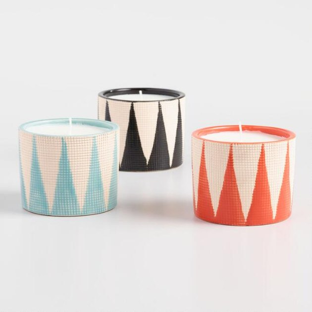 three candles with geometric patterns in blue, black, and orange