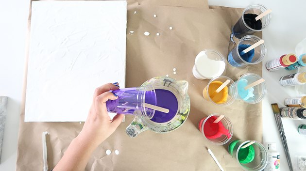 Pouring paint into measuring cup.
