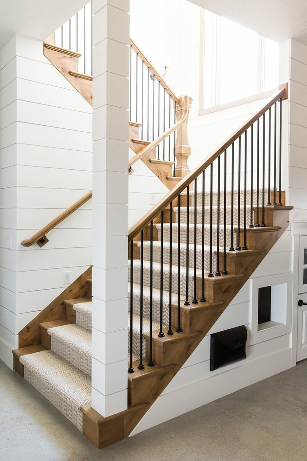 Rustic stair railing with beige stair runner and white shiplap