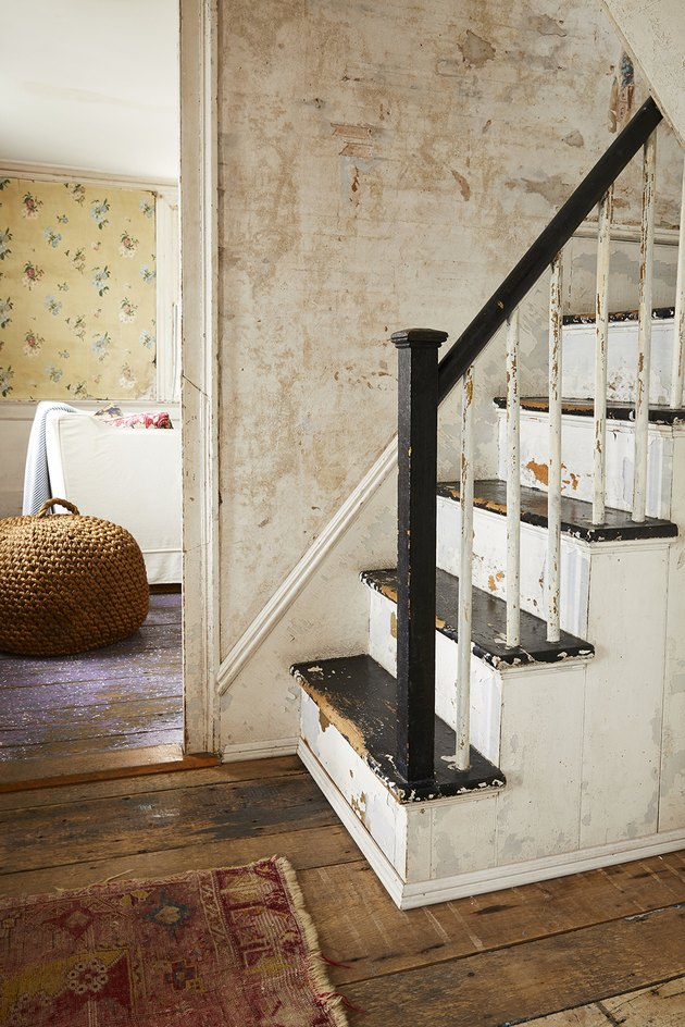 black and white rustic stair railing in hallway with wood floor and vintage rug