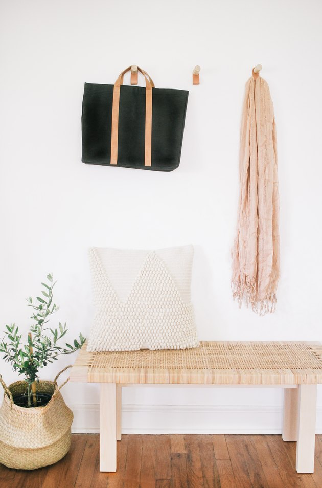 entryway idea with wood and leather wall hooks for bags and scarves above accent bench and plant in woven basket