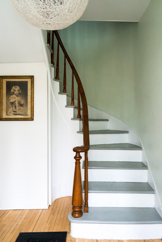 Rustic stair railing with white stair risers and wood railing in mint green entryway