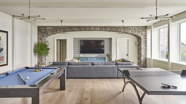 rustic man cave ideas with stone arch, pool table, and ping pong table