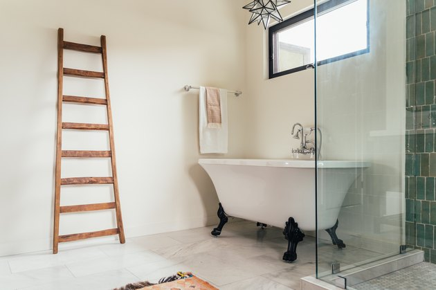 clawfoot tub with black angled legs, decorative wood ladder leaning on the wall, glass shower door with green vertical tiles