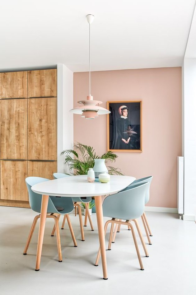 pink dining room with light blue chairs and pink pendant