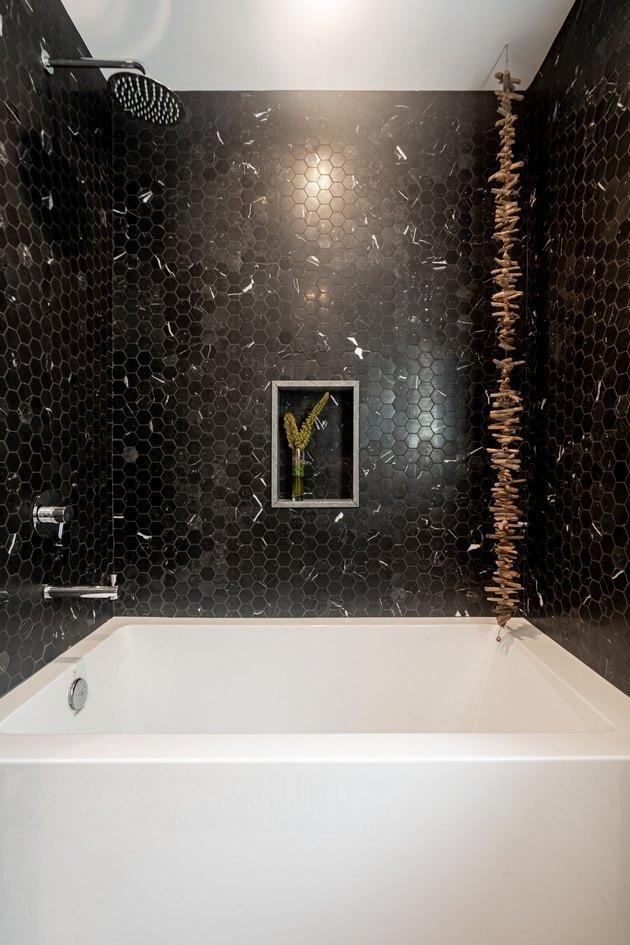 Black penny tile wall around white bathtub