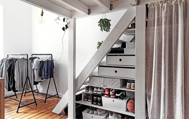bedroom storage idea under stairs hidden by IKEA curtains
