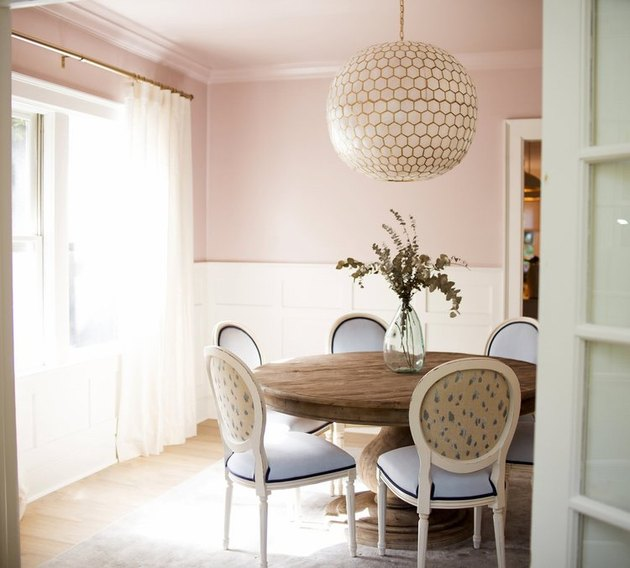 traditional pink dining room idea with white wainscoting