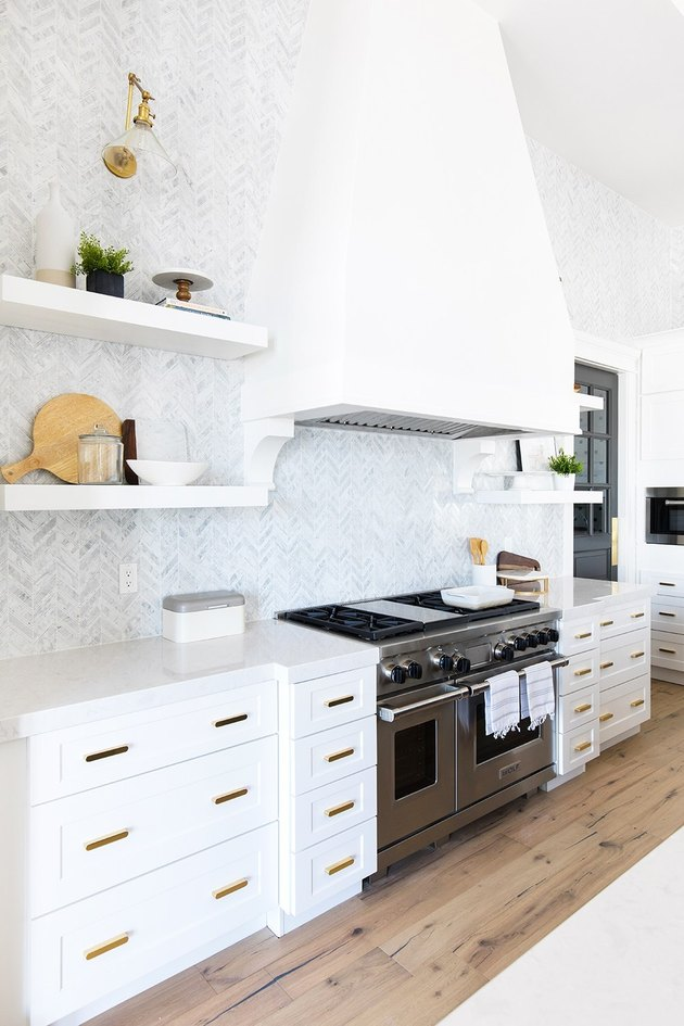 Modern kitchen idea with large white hood and tile backsplash