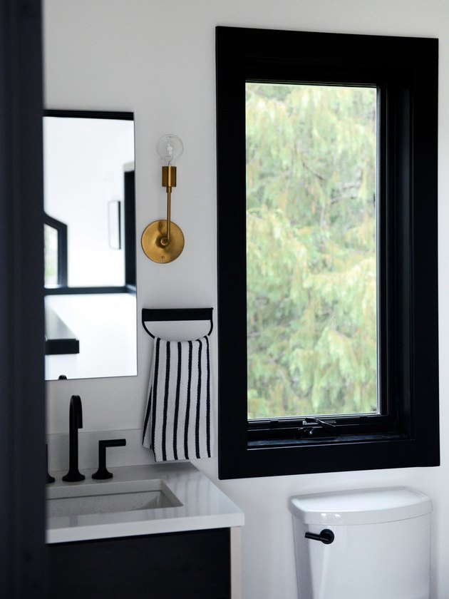 black and white bathroom with deck-mounted faucet on small vanity