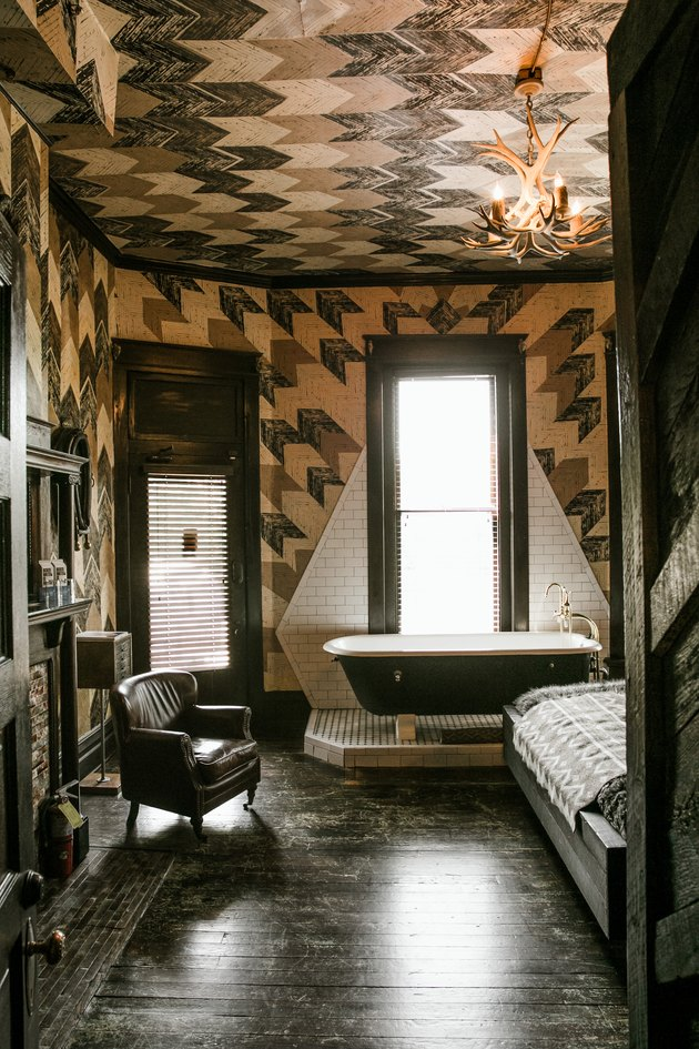 black clawfoot tub on a platform in a bedroom, patterned walls and ceiling, dark wood floors, an armchair and a bed are also seen in the room