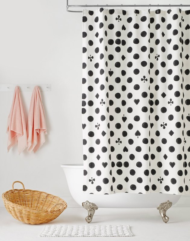 tub in bathroom with black and white curtain and two towels