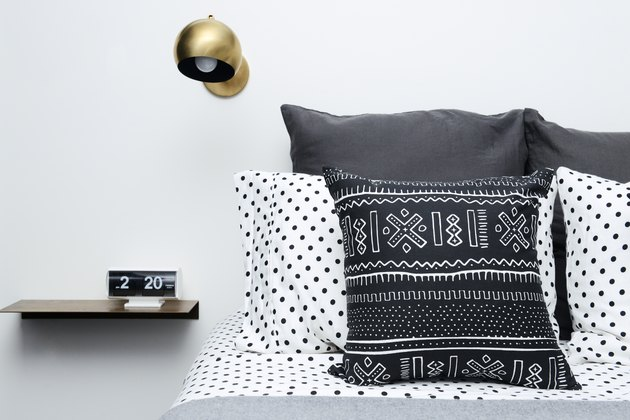 black and white bedding with gold sconce