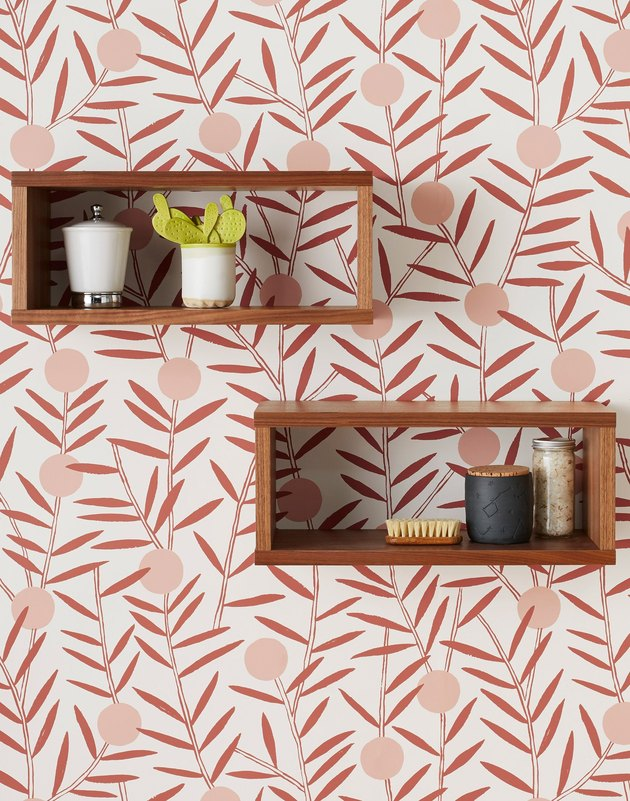 dusty rose floral wallpaper and two wooden shelves