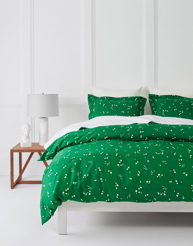 bed with green bedding and side table