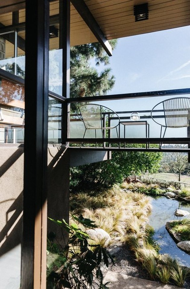 midcentury home with bridge-style balcony overlooking city and backyard stream