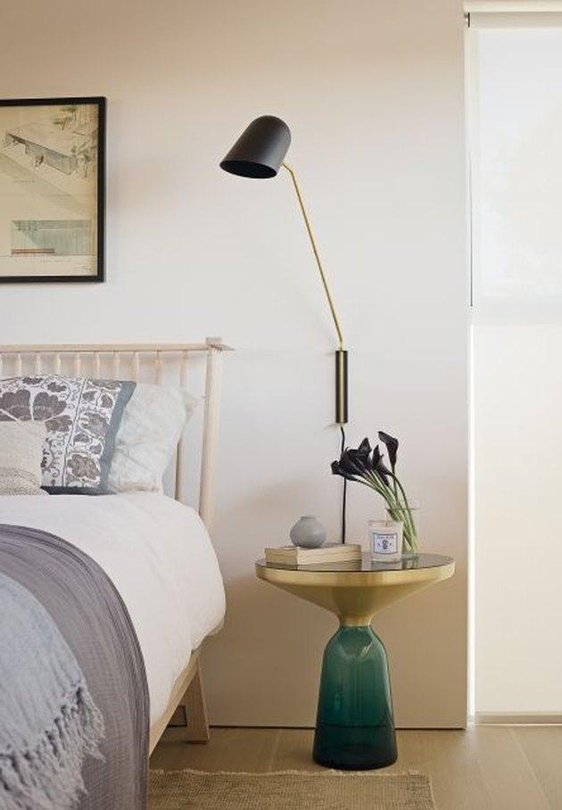 celadon colors on nightstand in beige bedroom with gray throw