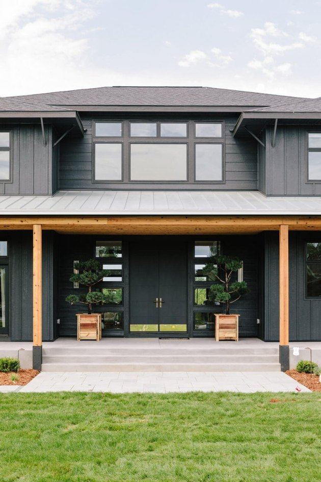 gray exterior window trim on two0level house with wood pillars and concrete porch