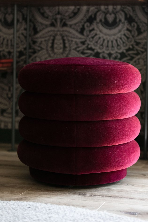 ferm LIVING jewel-tone round pouf next to patterned wallpaper