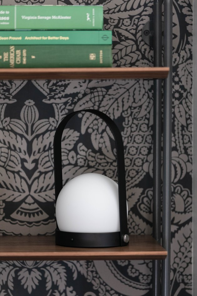 Menu portable LED lamp on bookcase next to patterned wallpaper