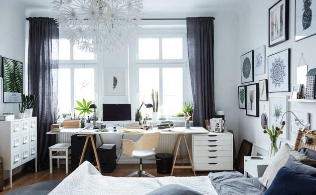bedroom office idea with industrial desk setup along a wall of windows in a mostly-white bedroom