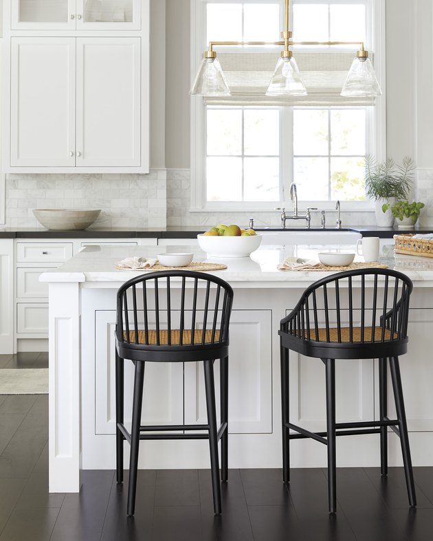 traditional kitchen lighting in white space with black stools