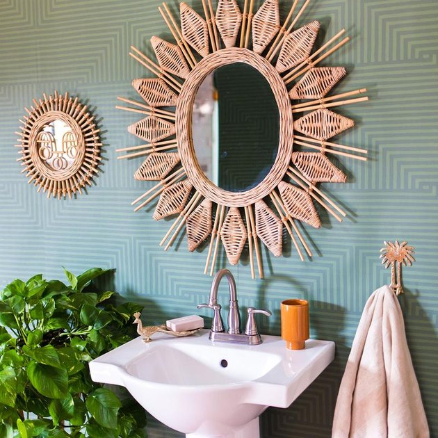 celadon colors in wallpaper in bathroom with rattan mirror