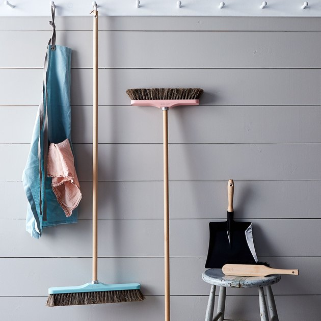 Push brooms against a gray wall.