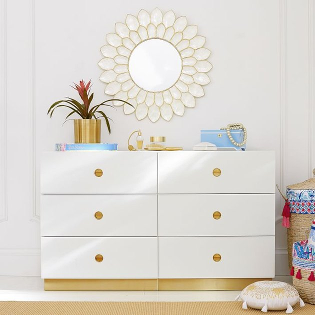 white six drawer dresser with brass base and drawer pulls