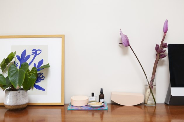 Flowers on credenza with art