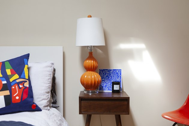 Midcentury nightstand with orange lamp