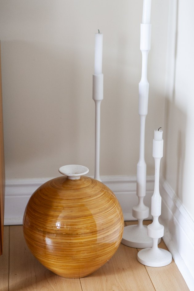 White tall candlesticks on floor with vase