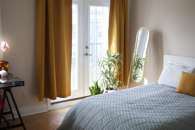 Bed with blue bedspread and gold curtains