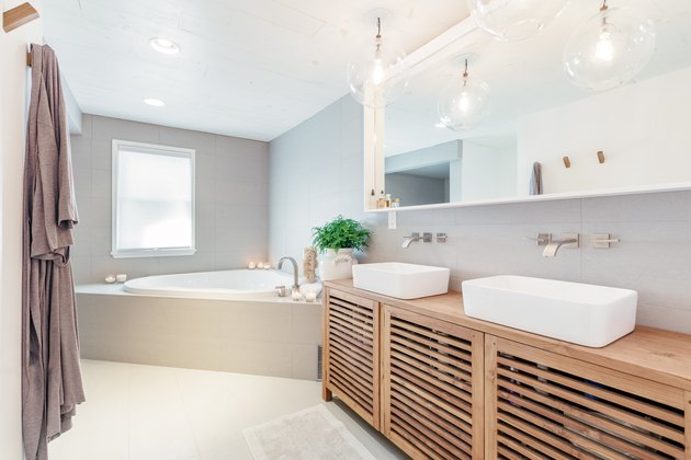 wood vanity with two white vessel sinks and wall-mounted faucets, corner drop-in bathtub with platform